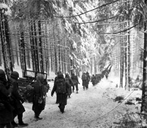 American soldiers of the 289th Infantry Regiment march along the snow-covered road on their way to cut off the St. Vith-Houffalize road in Belgium.  January 24, 1945.  Richard A. Massenge.  (Army) NARA FILE #:  111-SC-199406 WAR & CONFLICT BOOK #:  1079